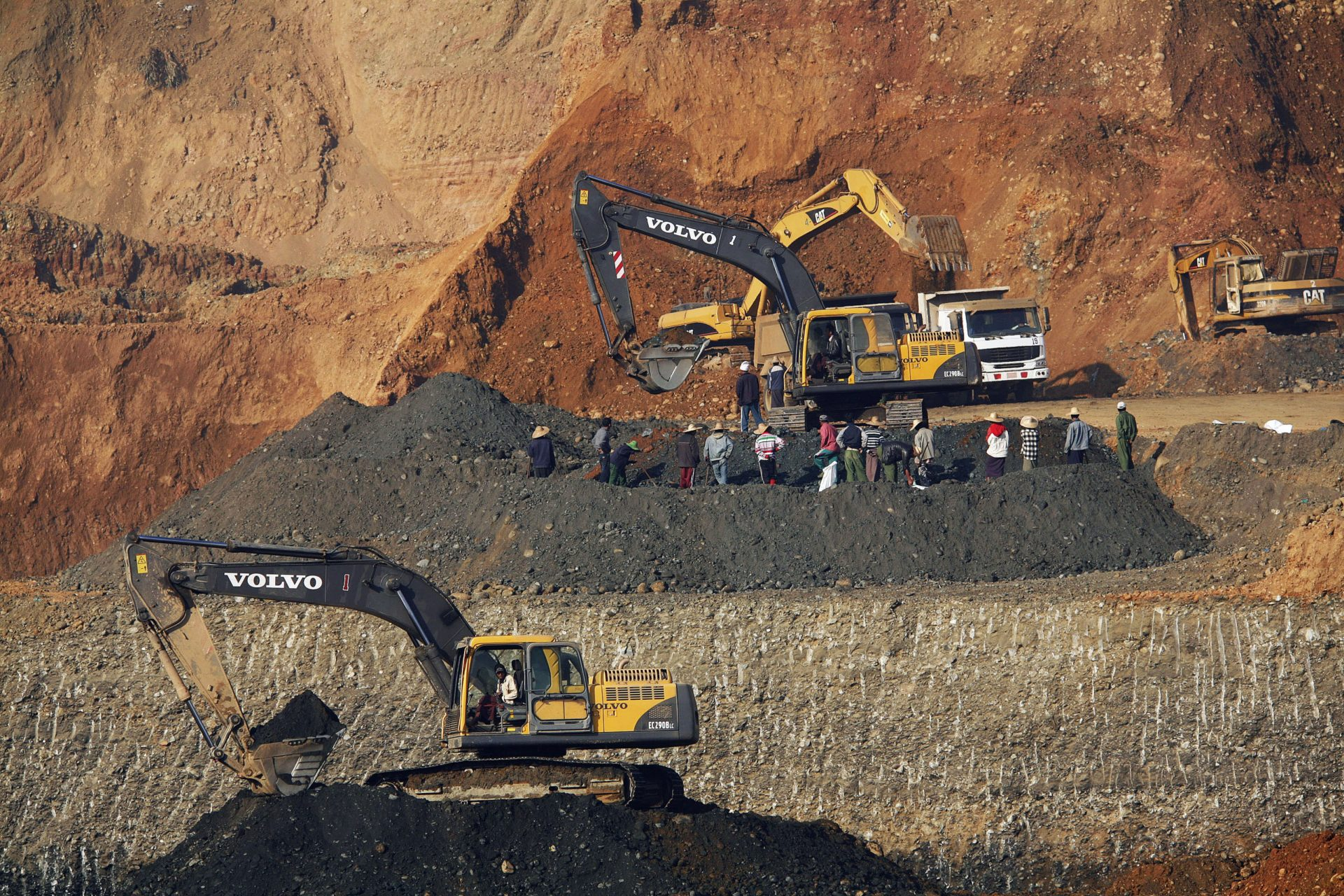 People gather around machines as they work at a jade mine in Pharkant township
